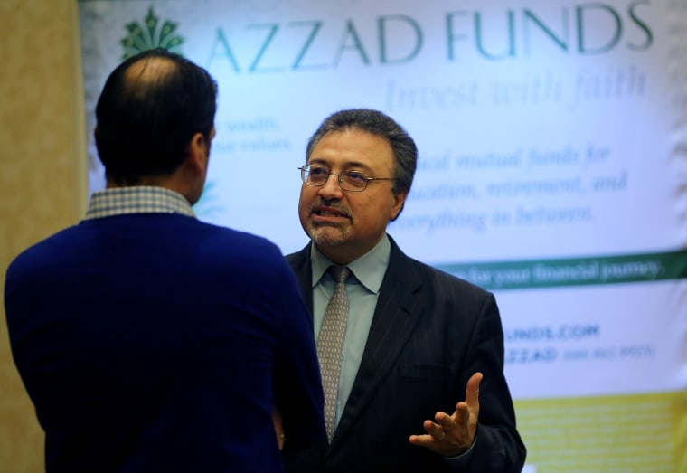 Image: Activist investor Bashar Qasem, President and CEO of Azzad Asset Management Inc, speaks to a client during a conference in Huntington Beach, California