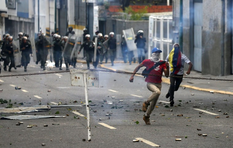 Image: Demonstrators run away during a rally against Venezuela's President Nicolas Maduro's government in Caracas