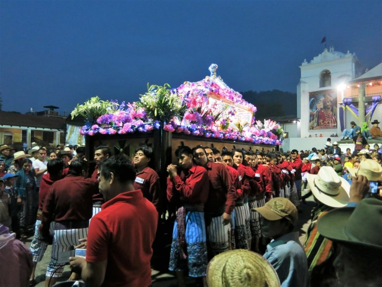 El Señor Sepultado—the statue of the buried Christ— is carried on a wooden platform by the village men in the traditional dress of Santiago Atitlan.
