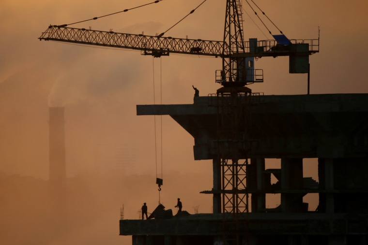 Image: People work atop a building under construction as sun sets in Pyongyang