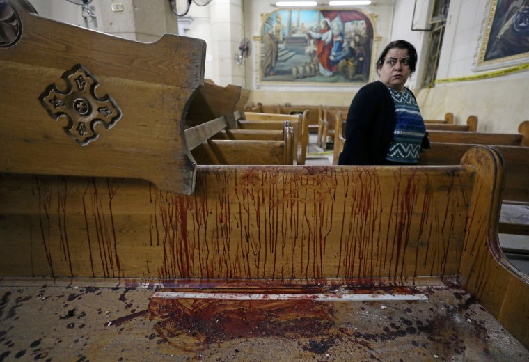 Image: A woman stands near a pew covered in blood inside a Coptic church that was bombed on Sunday in Tanta