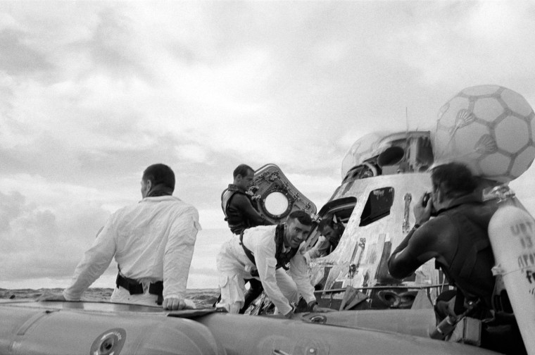 S70-35610 (17 April 1970) --- A water level view of the Apollo 13 recovery operations in the South Pacific Ocean. The three astronauts as seen egressing their spacecraft. John L. Swigert Jr. (back to camera), command module pilot, is already in the life raft. Fred W. Haise Jr., lunar module pilot, facing camera, is stepping into the life raft. James A. Lovell Jr., commander, is leaving the spacecraft in the background. A United States Navy underwater demolition team assists with the recovery operations. The three crewmembers were picked up by helicopter and flown to the prime recovery ship, USS Iwo Jima. The Apollo 13 Command Module (CM) splashed down at 12:07:44 p.m. (CST), April 17, 1970, to conclude safely a perilous space flight. Though the Apollo lunar landing mission was canceled, a disastrous loss of three astronauts was averted.