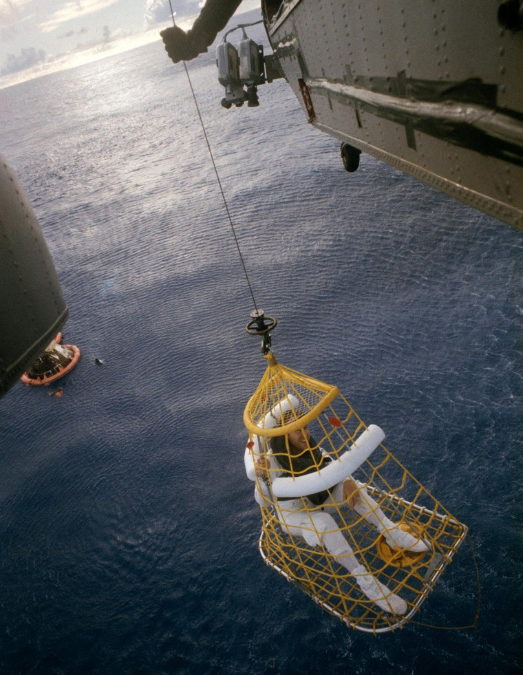 S70-35645 (17 April 1970) --- Astronaut James A. Lovell Jr., commander, is hoisted aboard a helicopter from the USS Iwo Jima, prime recovery vessel for the mission. Lovell was the last of the three Apollo 13 crewmembers to egress the Command Module (CM) and the last to be lifted aboard the helicopter. He was preceded by astronauts John L. Swigert Jr., command module pilot; and Fred W. Haise Jr., lunar module pilot. The CM and a U.S. Navy underwater demolition team swimmer can be seen in the ocean background. Apollo 13 splashed down at 12:07:44 p.m. (CST), April 17, 1970.