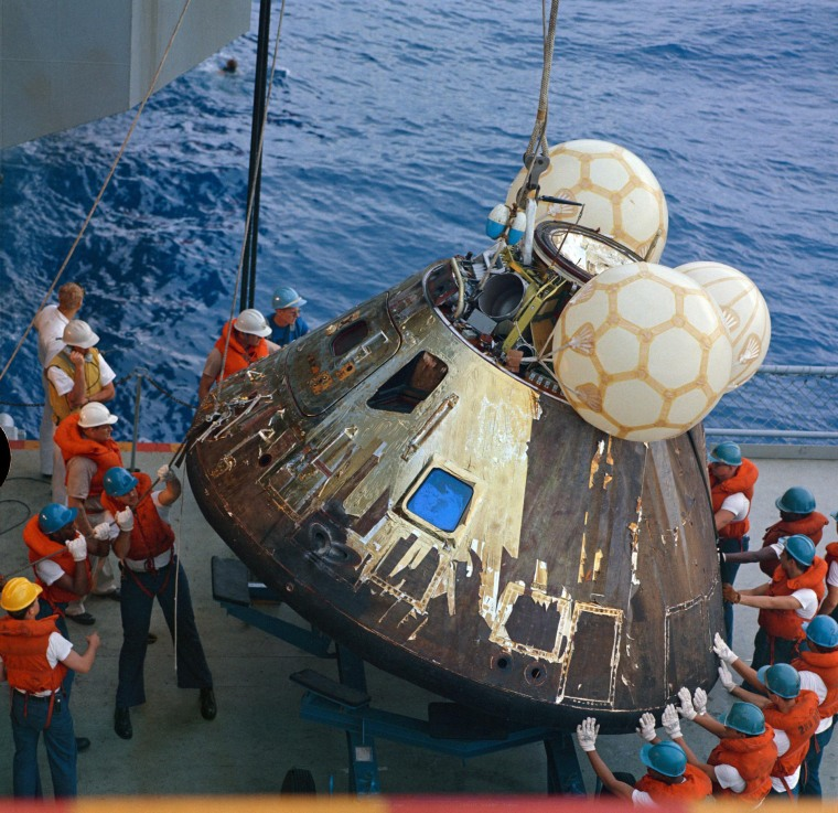 S70-35632 (17 April 1970) --- Crewmen aboard the USS Iwo Jima, prime recovery ship for the Apollo 13 mission, guide the Command Module (CM) atop a dolly onboard the ship. The CM is connected by strong cable to a hoist on the vessel. The Apollo 13 crewmembers, astronauts James A. Lovell Jr., commander; John L. Swigert Jr., command module pilot; and Fred W. Haise Jr., lunar module pilot, were already aboard the USS Iwo Jima when this photograph was made. The CM, with the three tired crewmen aboard, splashed down at 12:07:44 p.m. (CST), April 17, 1970, only about four miles from the recovery vessel in the South Pacific Ocean.