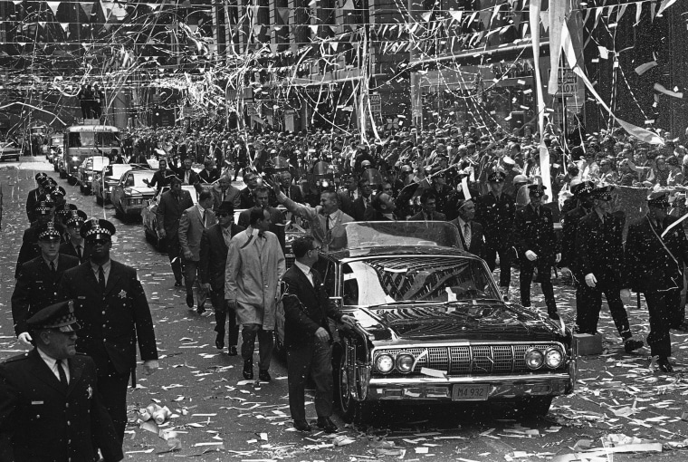 Confetti pours from the skyscrapers in Chicago?s financial district, May 1, 1970 as Apollo 13 astronauts John Swigert Jr., waving left, and James Lovell ride in a motorcade during a parade in their honor. (AP Photo)