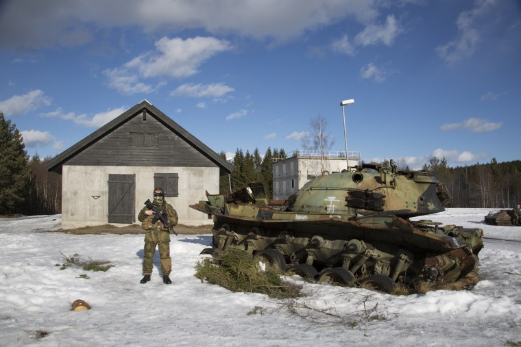Image: Tonje, a female soldier, stands by a the carcass of an old tank used for cover during the military exercises at Terningmoen Camp in Elverum, Norwa