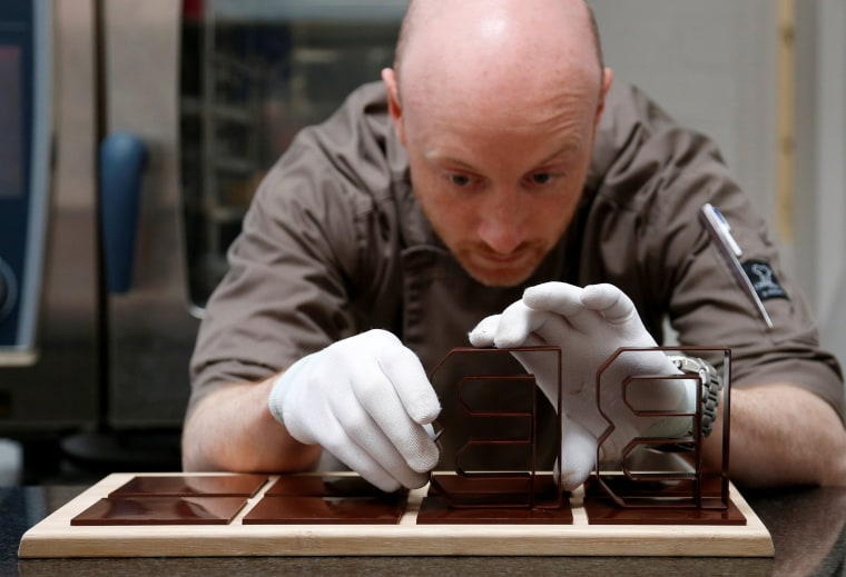 Image: Founder of the Miam Factory 3D printing chocolate company adjusts three-dimensional chocolate logos in Gembloux