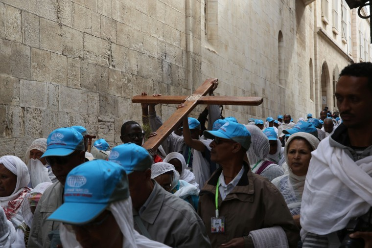 "Image: Christian pilgrims carry a wooden cross along the ""Via Dolorosa"" in Jerusalem's Old City Friday."