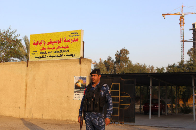 Image: Armed policemen guard the Baghdad Music and Ballet School's gates