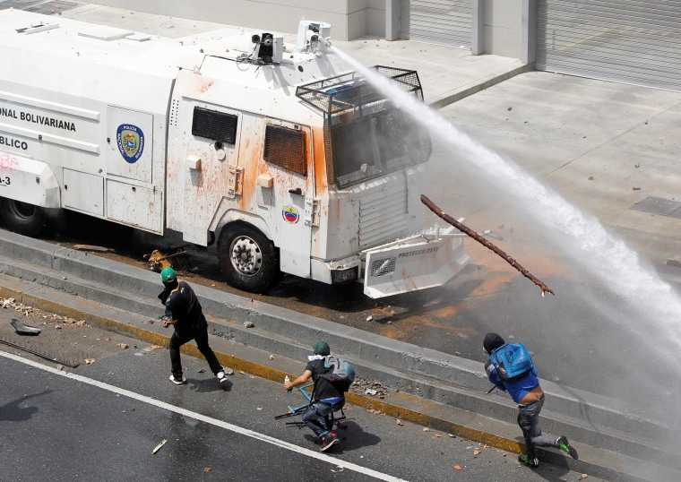 Image: Police water cannon disperses demonstrators during a protest in Venezuela