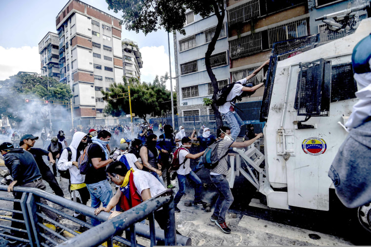Image: Protestors try to climb onto a water cannon vehicle during protests in Venezuela
