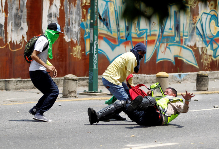 Image: Demonstrators grab a riot police officer during protests in Venezuela