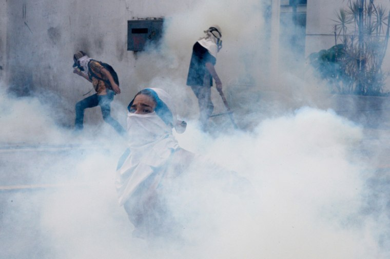 Image: Venezuelan opposition activists are are engulfed by a cloud of tear gas during a protest in Venezuela