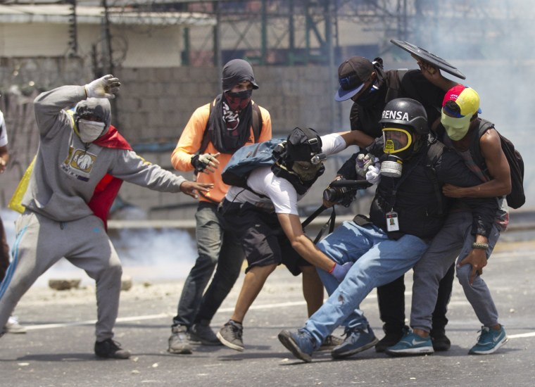 Image: Demonstrators help a journalist who was injured in a leg while covering the opposition rally Venezuela