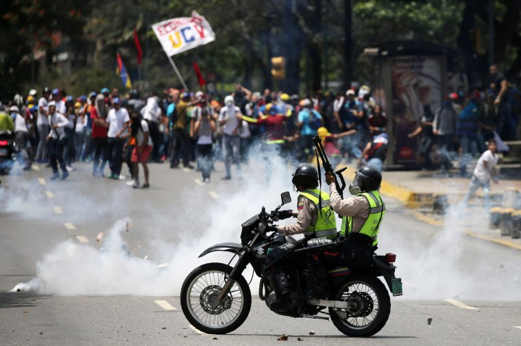 Image: Demonstrators clash with riot police at a rally in Venezuela