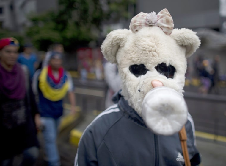 Image: A demonstrator wearing a home made teddy bear gasmask to protect himself from tear gas participates in a protest in Venezuela