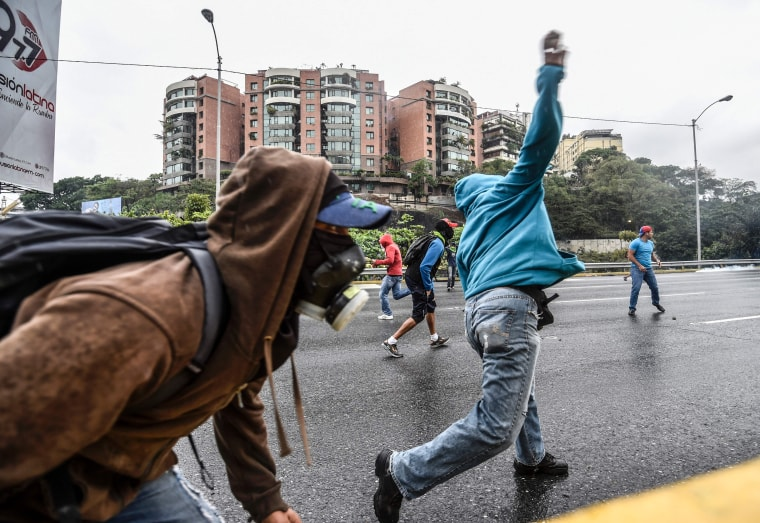 Image: Venezuelan opposition activists clash with riot police during a protest