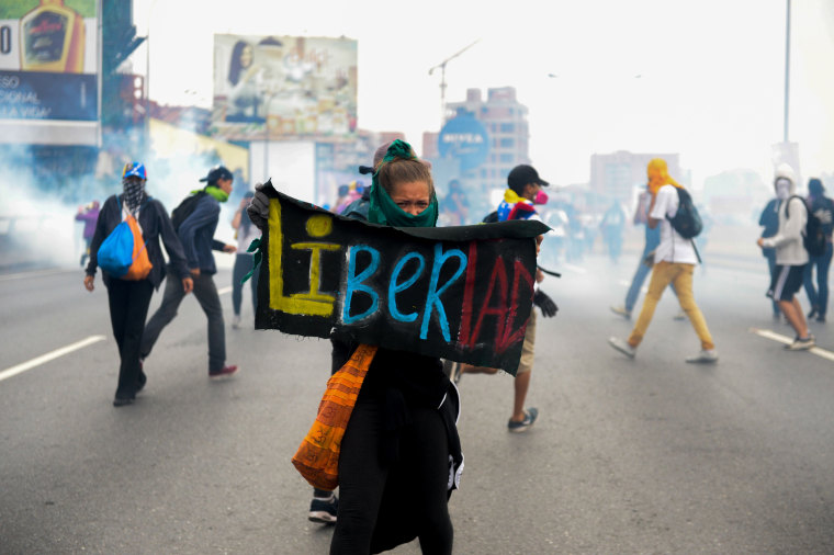 Image: A woman holds a sign stating Libertad during the opposition clash with riot police in Venezuela