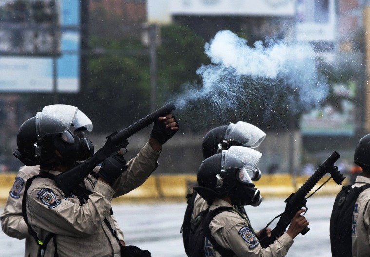 Image: Venezuelan National Guard personnel in riot gear crack down on a march of opposition activists protesting in Venezuela