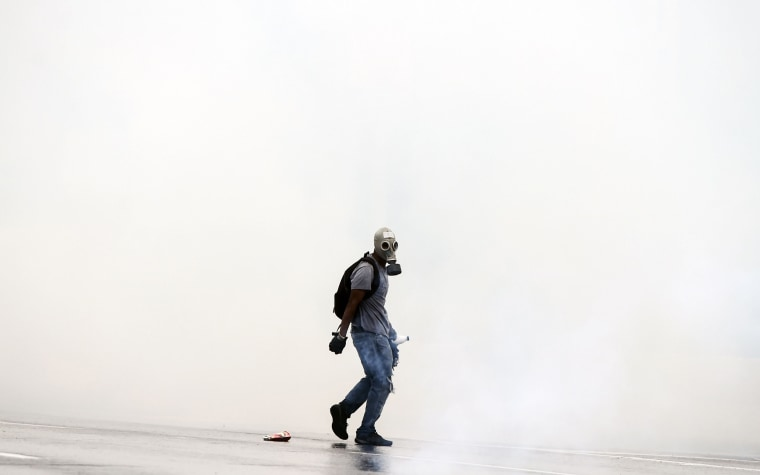 Image: Opposition activists clash with riot police while protesting in Venezuela