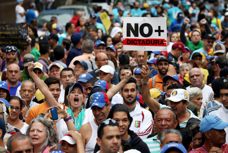 "Image: Demonstrators carrying a sign that reads ""No more dictatorship"" rally in Venezuela"