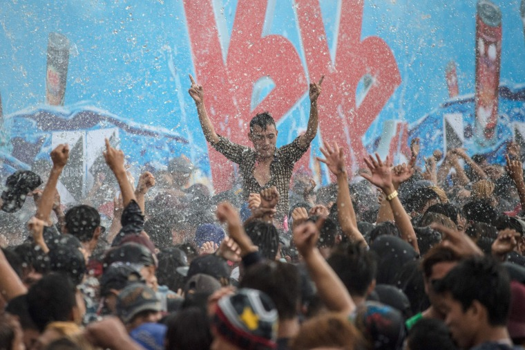 Image: Revelers dance to music as they are sprayed with water