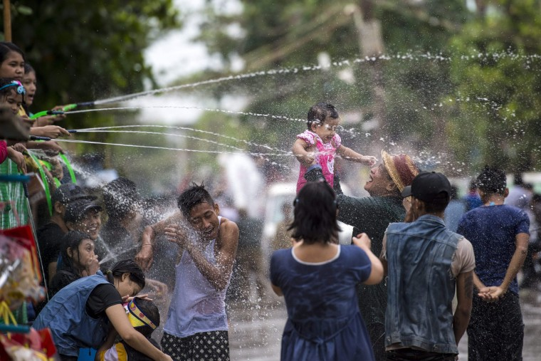 Image: A reveler holds up a child in Yangon