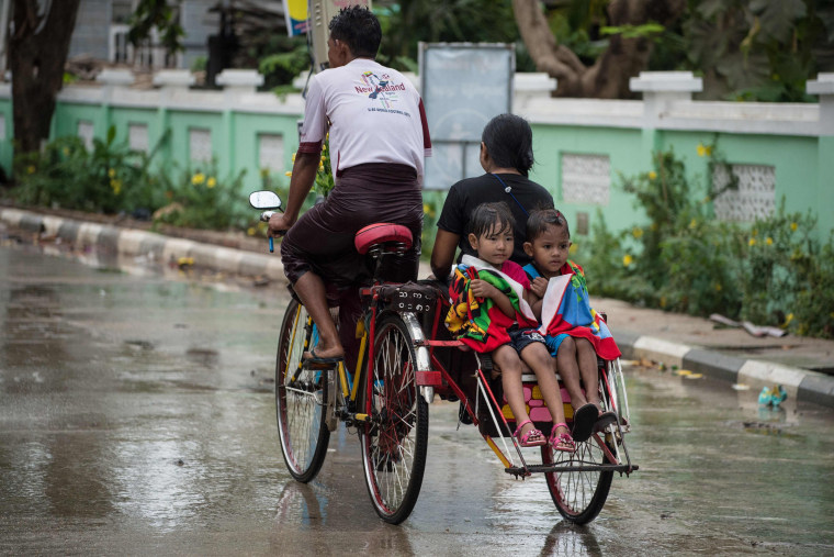 Image: Children are ferried on the back of a tricycle after being soaked with water