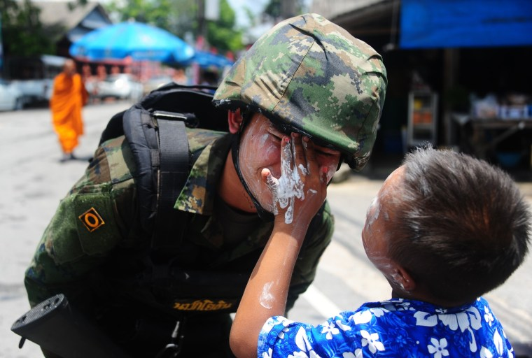 Image: A boy rubs powder on the face of a soldier during Songkran