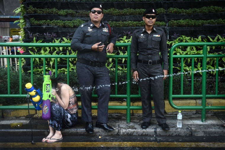 Image: Policemen watch as a woman is sprayed with water