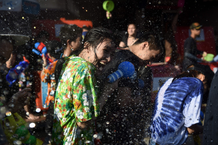 Image: A woman laughs as she gets soaked in water in Bangkok