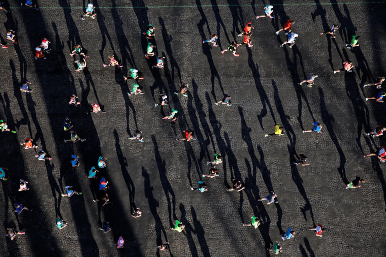 Image: Competitors run down the Champs Elysees below the Arc de Triomphe at the start of the 41st Paris Marathon in Paris