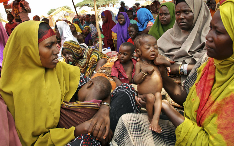Image: Newly displaced Somali mothers and their children sit in a camp in the Sahal area on the outskirts of Mogadishu