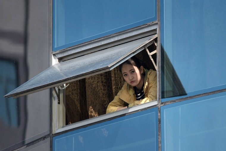 Image: A woman watches from a window as competitors run during the Pyongyang Marathon