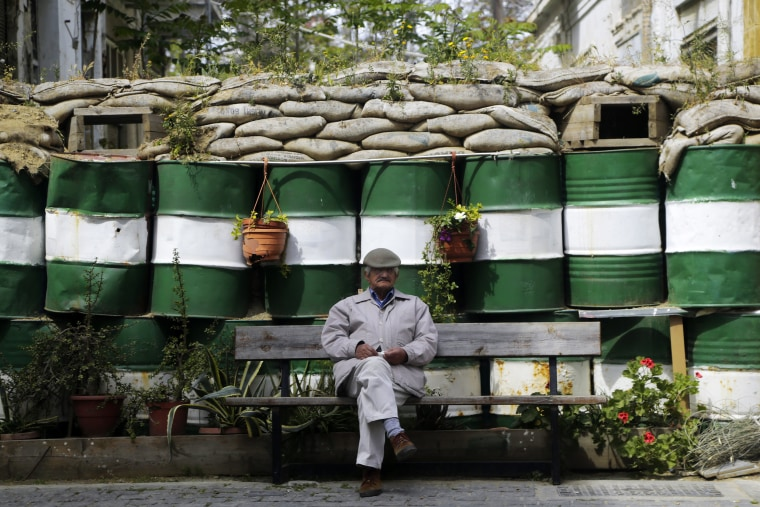 Image: An elderly man sit on a bench in front of the barrels and sandbags blocking a road crossing