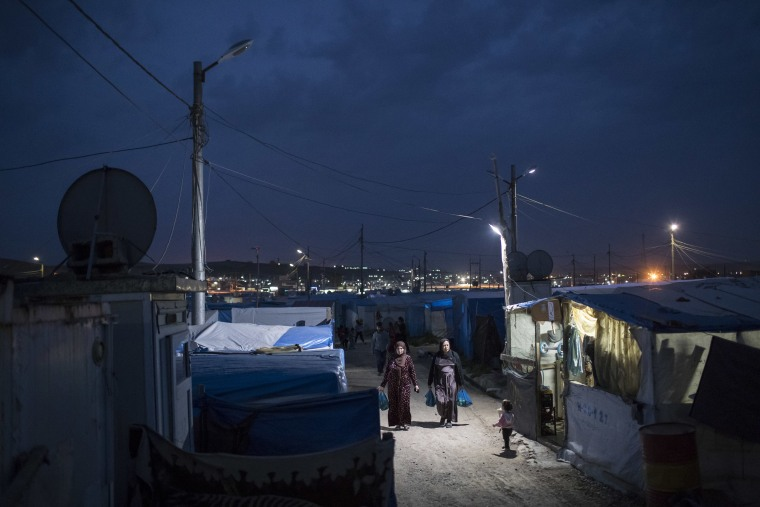 Image: Syrian women walk at dusk in the Kawergosk refugee camp in northern Iraq