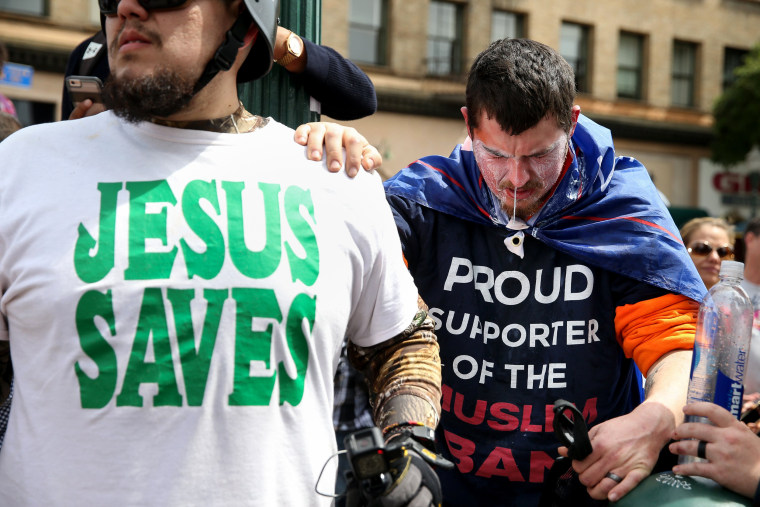 Image: A Trump supporter holds on to another man for support after being pepper sprayed by protesters at the Patriots Day rally in Berkeley.