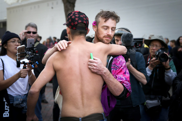 Image: A Trump supporter and a protester hug at amid fights in Berkeley.