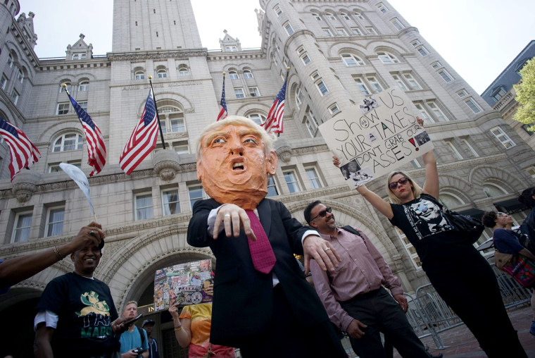 Image: Protesters walk by the Trump hotel during the Tax March in Washington, DC.