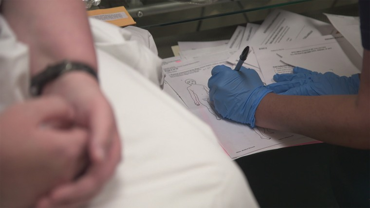 "Nurse writing on a rape kit diagram in ""I Am Evidence."""