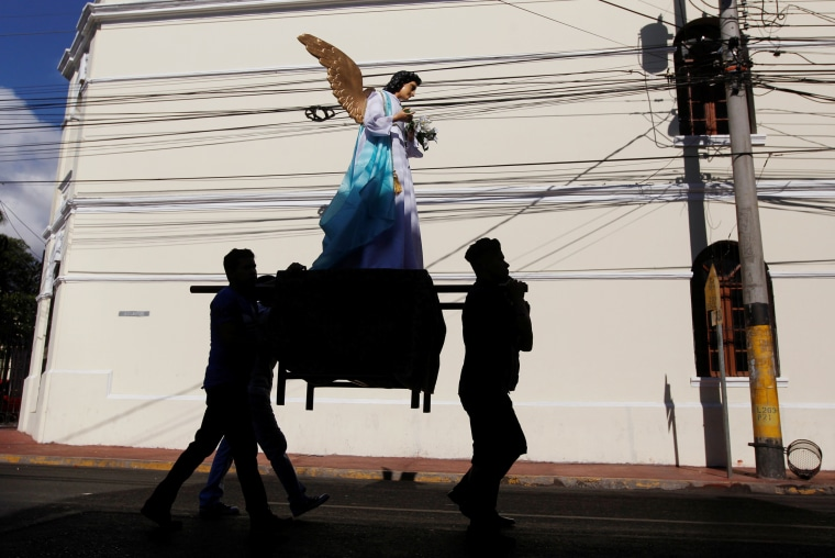 Image: People carry a statue as they participate in an Easter Sunday procession through the streets of Tegucigalpa