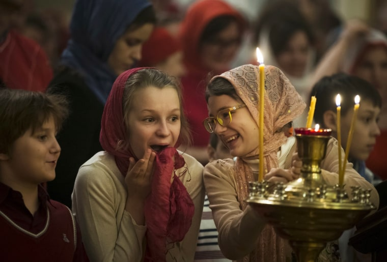 Image: Girls react during the Orthodox Easter service at the Church of the Holy Martyr Tatiana