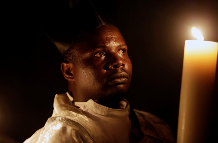 Image: A priest of the Legio Maria African Mission church carries a candle as he attend the easter vigil mass in Nairobi