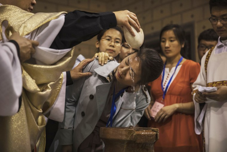 Image: Chinese Catholic Bishop Zhang Hong, left, pours holy water on the head of a worshipper during a special baptism ceremony on Holy Saturday