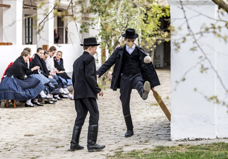 Image: Boys from the Hungarian folk dance ensemble Lajta play a Hungarian traditional ballgame