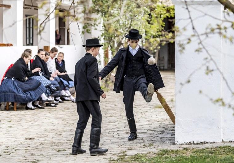 Image: Boys from the Hungarian folk dance ensemble Lajta play a Hungarian traditional ballgame