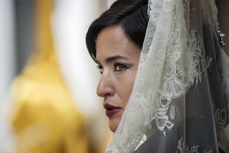 Image: A woman wearing a white mantilla over her head takes part in a procession on Easter Sunday in Jaen, Andalusia, southern Spain