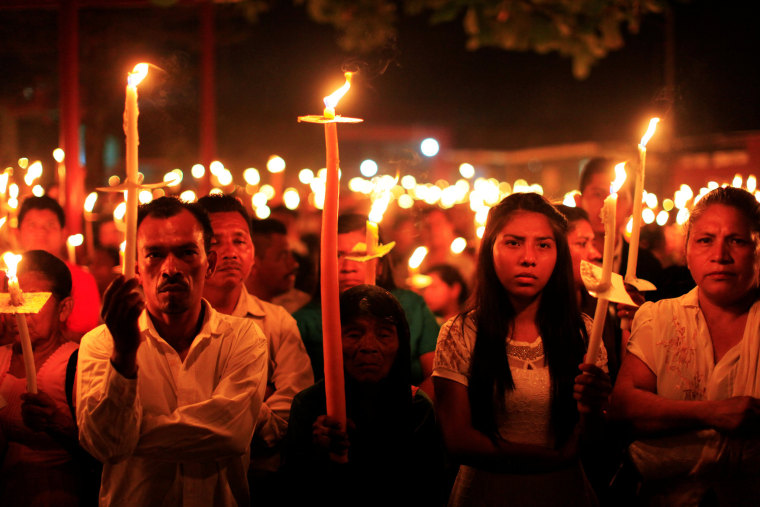 Image: Catholics take part in the Procession of Lights, as part of the Holy Week celebration in Nahuizalco