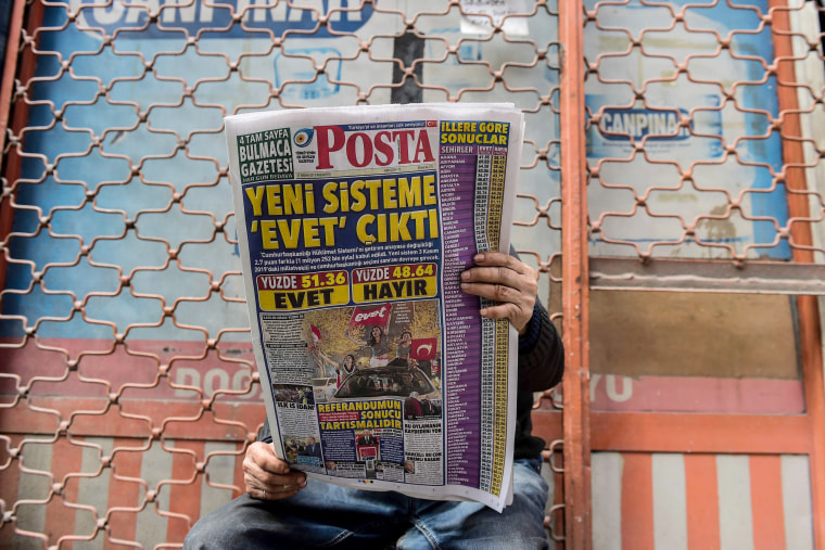 """Image: A man reads Posta newspaper bearing a headline which translates as \""""Yes to New System\"""" in Istanbul on April 17."""