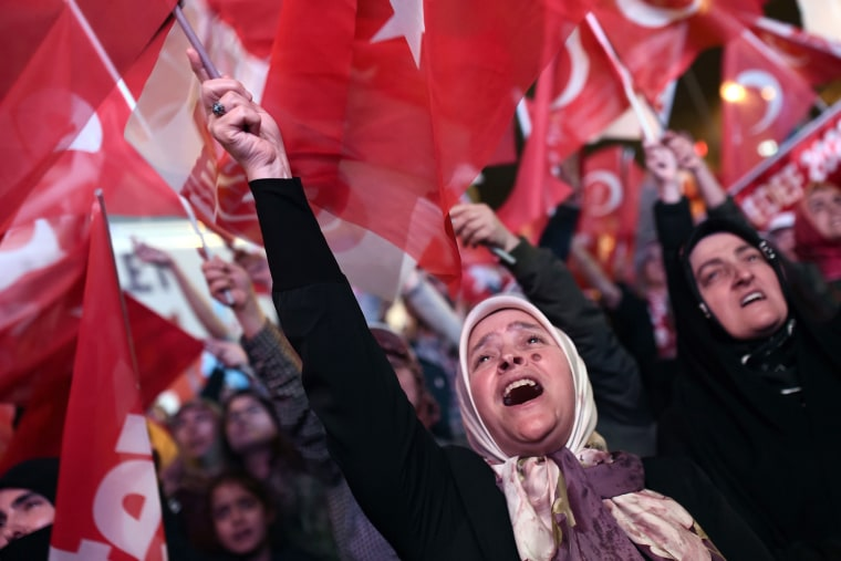 Image: A woman supporting Turkish President Recep Tayyip Erdogan waves a Turkish national flag as she celebrates during a rally near the headquarters of the conservative Justice and Development Party (AKP) on April 16, 2017, in Istanbul.
